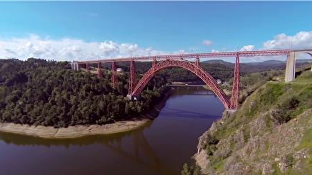 红色的铁桥在绿色的大自然中显得格外耀眼。(视频截图)