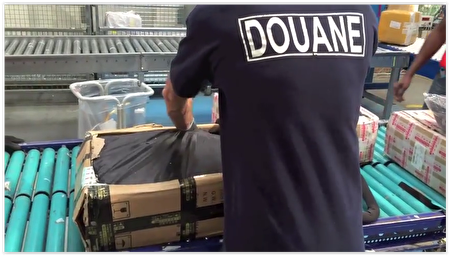 法国海关人员在拆开中国 冒牌婴儿推车。(视频截图)