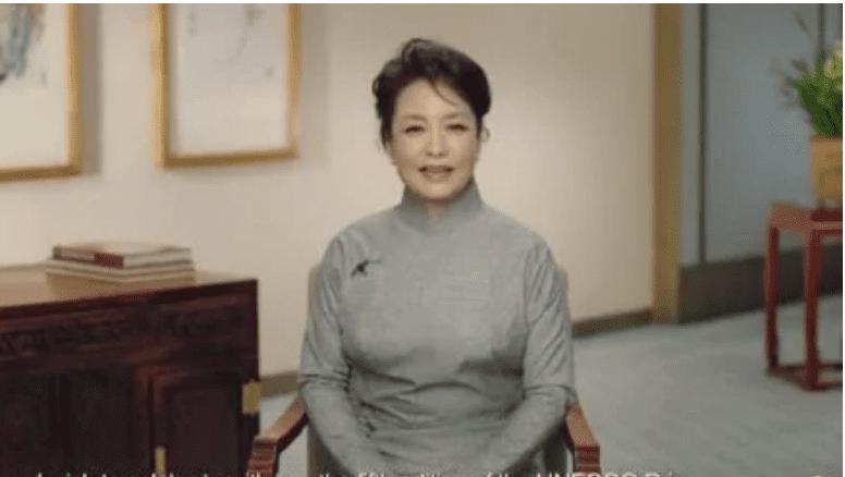 官媒发布的影片中,彭丽媛一身灰色旗袍,坐在椅子上。(视频截图)